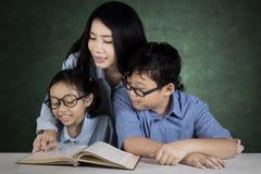 Due studenti con l'insegnante nell'aula Fotografia Stock