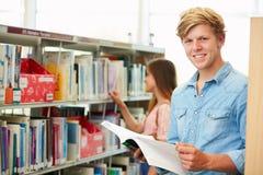 Due studenti di college che studiano nella biblioteca immagini stock libere da diritti