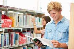 Due studenti di college che studiano nella biblioteca fotografia stock libera da diritti