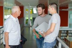 Due studenti ed il loro conferenziere in corridoio Immagini Stock