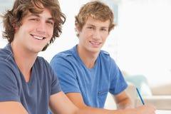 Due studenti maschii che esaminano la macchina fotografica e sorridere Immagini Stock