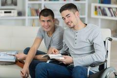 Due studenti maschii che esaminano macchina fotografica mentre sorridono Immagine Stock Libera da Diritti