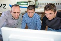 Due studenti maschii ed il loro professore in computer anteriore Fotografie Stock
