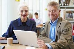 Due studenti maturi che lavorano insieme nella biblioteca facendo uso del computer portatile Fotografia Stock