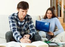 Due studenti seri che preparano per l'esame insieme al computer portatile Fotografia Stock