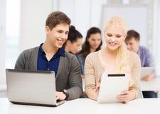 Due studenti sorridenti con il pc della compressa e del computer portatile Fotografie Stock