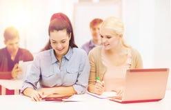 Due studenti sorridenti con il pc della compressa e del computer portatile immagine stock