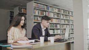 Due studenti universitari caucasici che preparano all'esame in biblioteca video d archivio