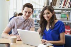 Due studenti universitari che lavorano nella biblioteca facendo uso del computer portatile Fotografia Stock Libera da Diritti