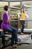 Due studenti universitari femminili che comunicano nella libreria Fotografia Stock Libera da Diritti