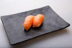 Due sushi di color salmone freschi su un piatto nero Fotografia Stock Libera da Diritti