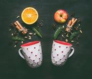 due tazze bianche con gli ingredienti per produrre il vin brulé del nuovo anno, arancia, cannella, anice ed i chiodi di garofano, fotografie stock