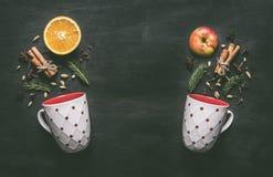 Due tazze bianche con gli ingredienti per produrre il vin brulé, l'arancia, la cannella, l'anice ed i chiodi di garofano del nuov fotografie stock libere da diritti