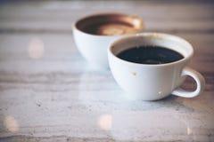 Due tazze bianche del caffè caldo del latte Immagine Stock