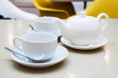 Due tazze bianche del tè con i cucchiai ed i piattini brillanti Immagine Stock