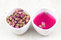 Due tazze bianche delle rose di tè su una tavola di legno Fotografia Stock