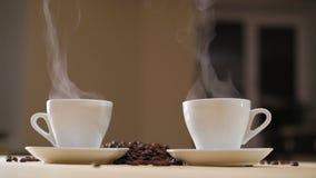 Due tazze bianche di caffè delizioso sulla tavola con i semi di cacao torrefatti in 4K stock footage