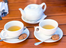 Due tazze bianche di tè e cucchiai con i biscotti Immagine Stock