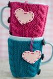 Due tazze blu in maglione blu e rosa con i cuori Immagine Stock Libera da Diritti