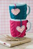 Due tazze blu in maglione blu e rosa con i cuori Fotografia Stock