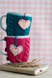 Due tazze blu in maglione blu e rosa con i cuori Fotografia Stock Libera da Diritti