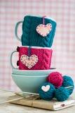 Due tazze blu in maglione blu e rosa con i cuori del feltro Fotografie Stock