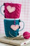 Due tazze blu in maglione blu e rosa con i cuori del feltro su un taccuino Immagini Stock Libere da Diritti