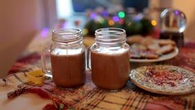 Due tazze con cacao e le caramelle gommosa e molle sono sulla tavola di Natale archivi video