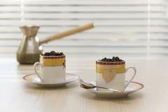 Due tazze con i chicchi di caffè Fotografia Stock