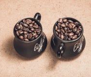 Due tazze con i chicchi di caffè su fondo di legno Immagini Stock