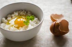 Due tazze con il tuorlo d'uovo fresco è sulla cima di riso giapponese fotografia stock