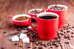 Due tazze con la tazza di caffè con i chicchi di caffè di legno del fondo dei chicchi di caffè intorno alle tazze rosse Fotografia Stock Libera da Diritti