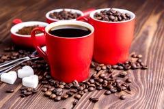 Due tazze con la tazza di caffè con i chicchi di caffè di legno del fondo dei chicchi di caffè intorno alle tazze rosse Immagini Stock Libere da Diritti