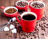 Due tazze con la tazza di caffè con i chicchi di caffè di legno del fondo dei chicchi di caffè intorno alle tazze rosse Immagine Stock Libera da Diritti