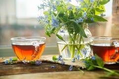 Due tazze dei fiori di estate e del tè Fotografie Stock