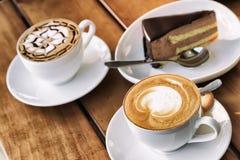 Due tazze del caffè del cappuccino e della mousse di cioccolato agglutinano Fotografie Stock Libere da Diritti
