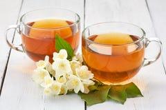 Due tazze del tè del gelsomino e fiori del gelsomino su una tavola bianca Fotografia Stock Libera da Diritti