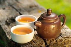Due tazze della teiera dell'argilla del cinese e del tè nero sul vecchio verro di legno Immagine Stock