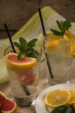 Due tazze di acqua di vetro con l'arancia, il limone, la menta ed il ghiaccio rossi Franco Fotografia Stock