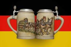 Due tazze di birra sui precedenti della bandiera Fotografia Stock