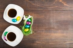 Due tazze di caffè bianche con le uova di cioccolato in copertura con la copia Fotografie Stock Libere da Diritti