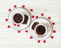Due tazze di caffè ceramiche con i cuori rossi sul backgro di legno Fotografia Stock