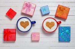 Due tazze di caffè con cuore modellano il simbolo ed i contenitori di regalo Fotografia Stock