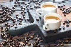 Due tazze di caffè con i chicchi di caffè Immagine Stock