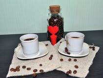 Due tazze di caffè con i chicchi ed il cuore di caffè Fotografia Stock
