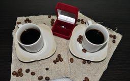 Due tazze di caffè con i chicchi ed il cuore di caffè Immagini Stock