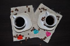 Due tazze di caffè con i chicchi ed il cuore di caffè Immagine Stock