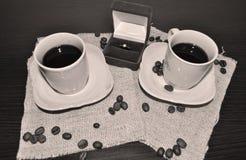 Due tazze di caffè con i chicchi ed il cuore di caffè Fotografie Stock