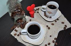 Due tazze di caffè con i chicchi ed il cuore di caffè Fotografia Stock Libera da Diritti