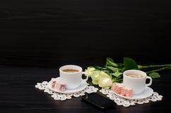 Due tazze di caffè con latte, smartphone, lukum su un piattino, rose bianche su un fondo nero Fotografie Stock Libere da Diritti